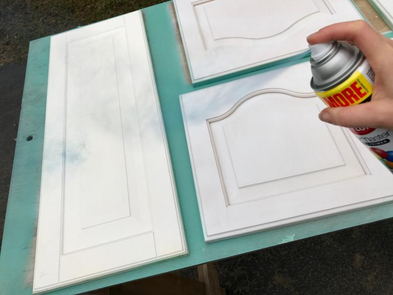 Theresa spray paints the cabinet doors.
