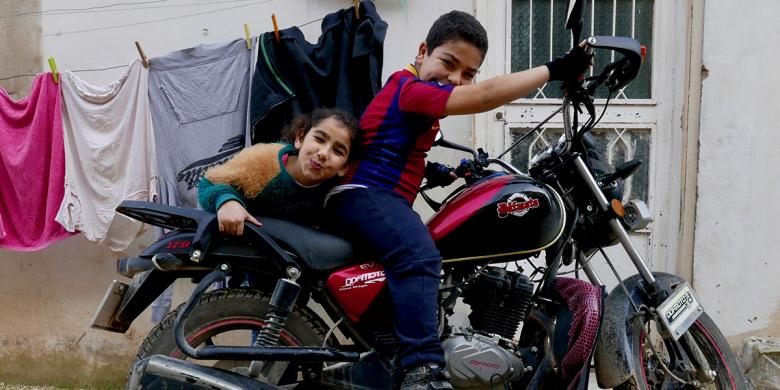 Photo: two children from sitting on a motor bike