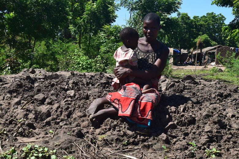 Photo: Grace sitting on mud where her house used to stand before it was taken by floods