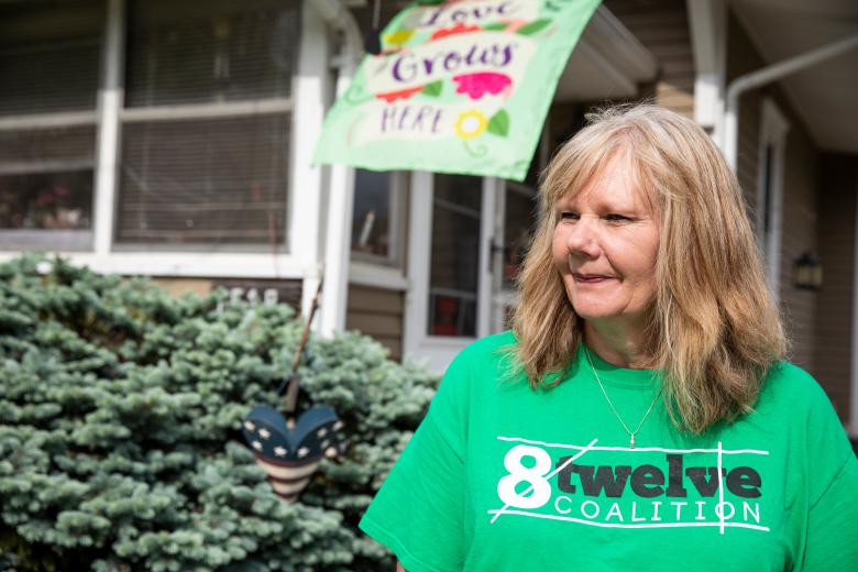 "Women in a T-shirt that says ""8 twelve"" stands in front of a home."
