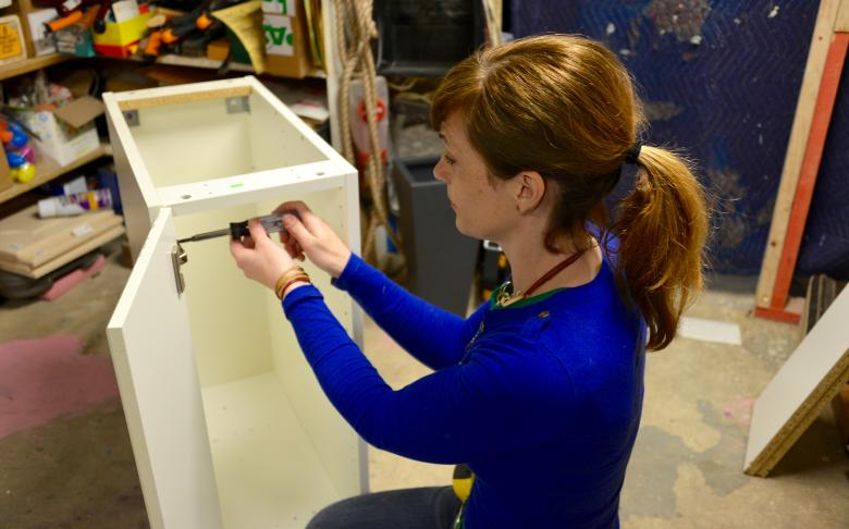 Theresa removes the hinges from the cabinet.