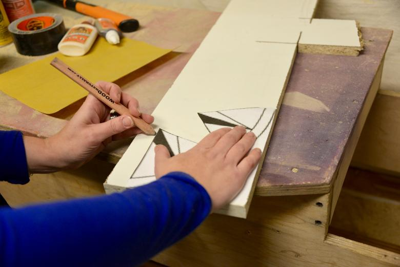 Theresa traces the paper template onto wood.