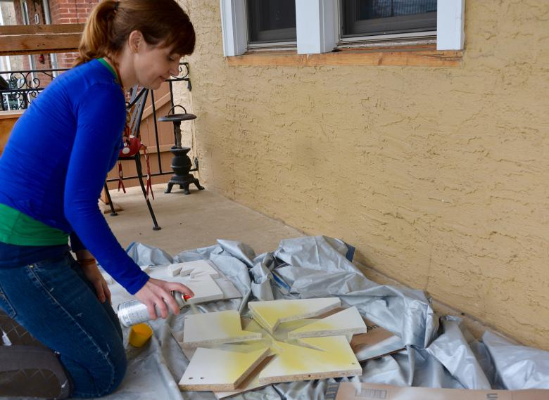Theresa spray paints the wooden pieces.
