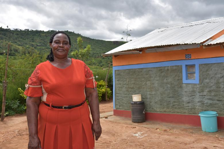 Photo: Jane Mueni Paul from Kenya standing in front of her newly built house