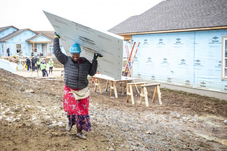 Noella carries a board of insulation above her head as she works on her home.