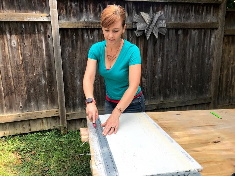 Theresa cuts with a utility knife.