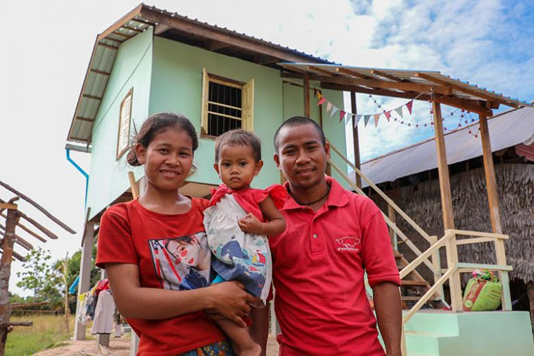 Chea and her husband Phlen with their child in front of their home completed during Cambodia Big Build 2019.