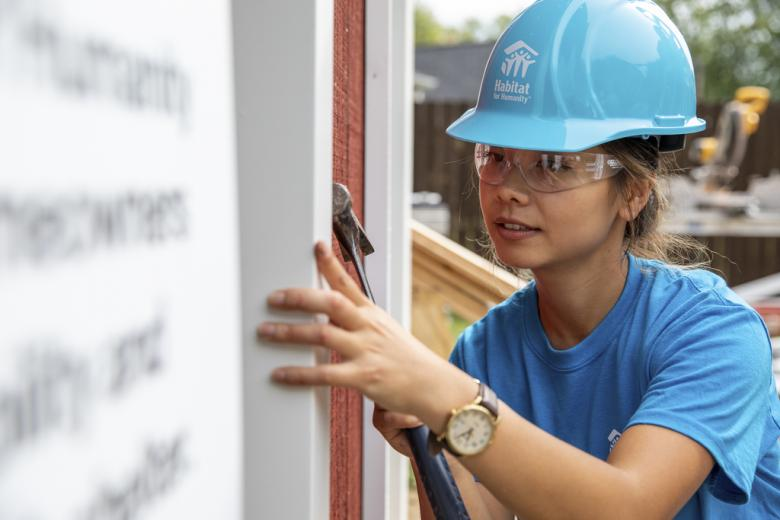 A young woman in a blue hard hat works on the siding of her future Habitat home.