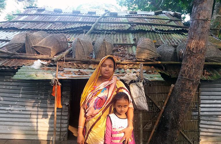 Sakina and her daughter Sadia in front of their old house in Bangladesh