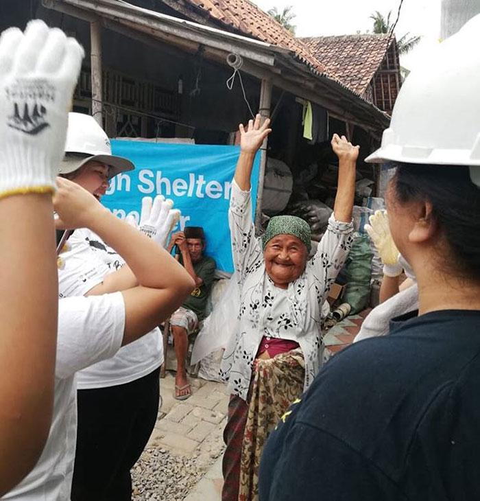 Atun, with raised hands, bonding with the volunteers working on her new home.