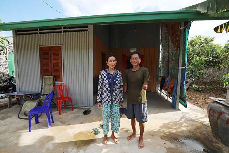 Samuth and her husband Bunthoeun in front of their house in cambodia's Kandal province