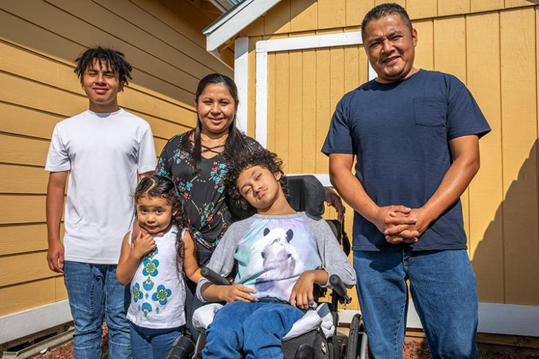 Parents with three kids, including one child in a wheelchair, in front of their home.