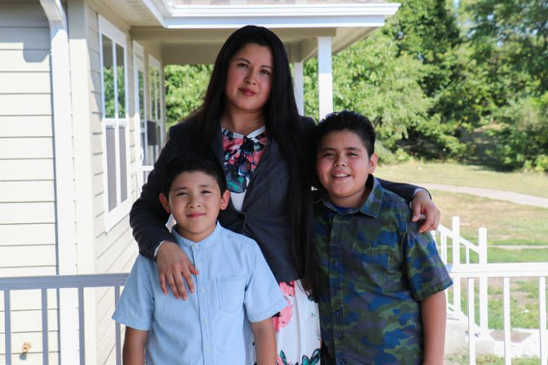 Claudia with her two young sons standing on their porch.