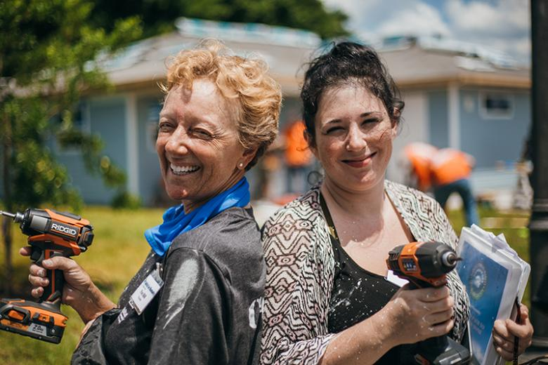 Two women holding drills and smiling on a build site.