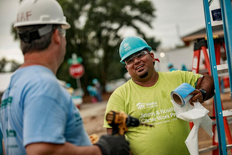 Man in green shirt and hard hat smiling while working on build site.