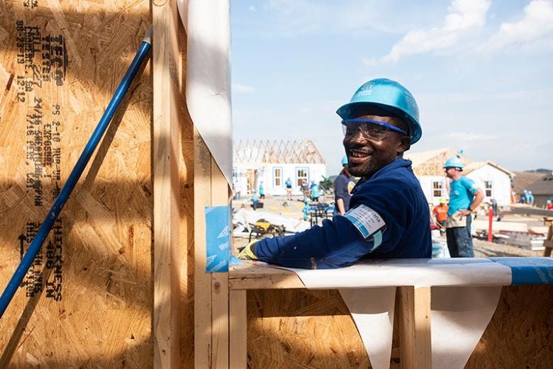 Man in hard hat smiling on build site.