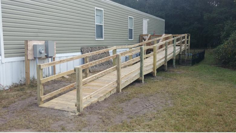 A long wooden ramp leading up to a pale green house.