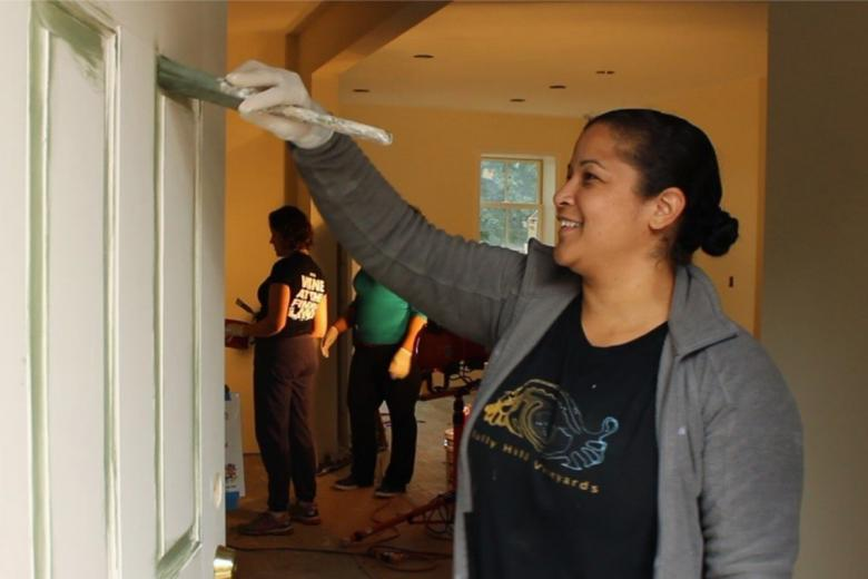 Nilda painting the door of her Habitat house.