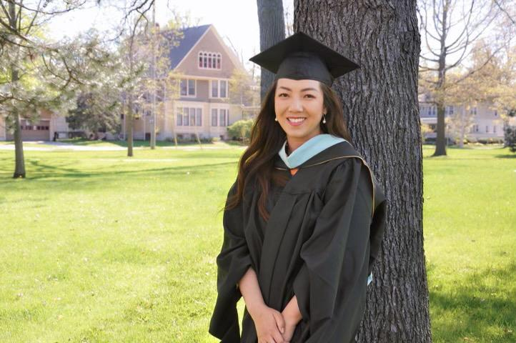 Ai posing by a tree in her graduation cap and gown.