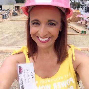 Volunteer Teri on a Habitat build site wearing a pink hardhat.